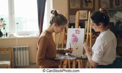 Female student of art school is painting flowers with oil paints while her teacher good-looking young woman is giving her advice pointing at picture.