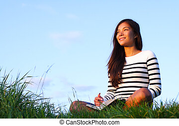 Woman studying outside in evening light with copy space. Beautiful mixed asian / caucasian woman.