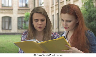 Female student points her forefinger into the journal outdoors