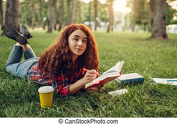 Female student preparing for exams on the grass