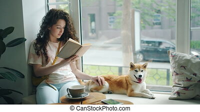 Female student reading book and stroking pet dog sitting on...