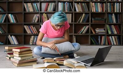 Female student researching with books and laptop
