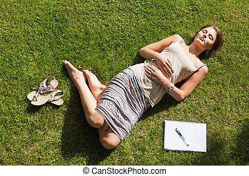 Female student resting on grass at the park