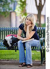 Female student sitting on bench