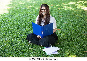 Female student sitting on the lawn