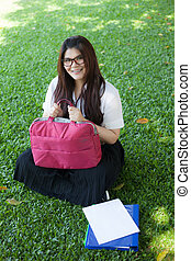 Female student sitting on the lawn.