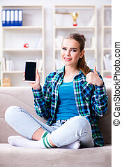 Female student sitting on the sofa with mobile