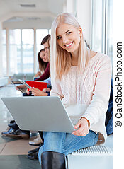 Female student sitting with laptop