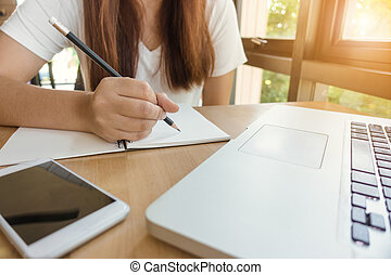 Female student taking notes from a book at library. Young asian woman sitting at table doing assignments in college library. Vintage effect style pictures.