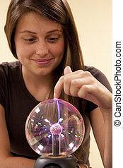 Female student touching a plasma ball.