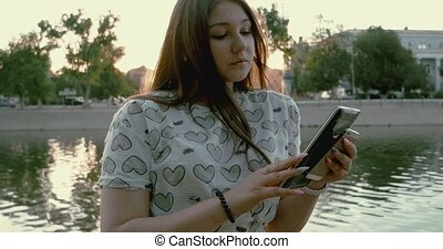 Female student using tablet pc in the park.
