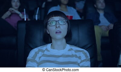 Female student watching sad drama in cinema touching face...