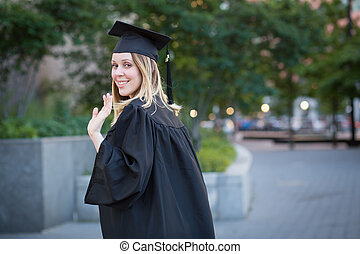 Female student waving hand at graduation on college campus