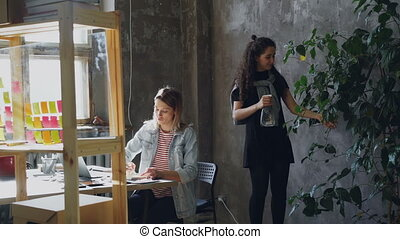 Female student with blond hair is working on project and drawing in notepad while her friend is spraying large green plant. Girls are socializing and smiling.