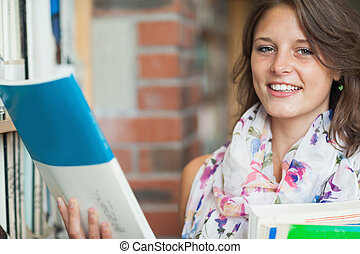 Female student with books by the shelf in library