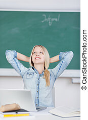 Female Student With Hands Behind Head Day Dreaming At Desk
