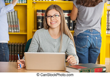 Female Student With Laptop Sitting At Table In Library
