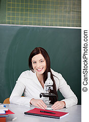 Female Student With Microscope At Desk In Classroom