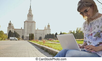 Female student working with a laptop on a square on the background of Lomonosov Moscow State University.