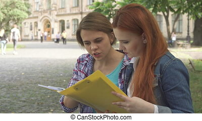 Female students look at some journal on campus