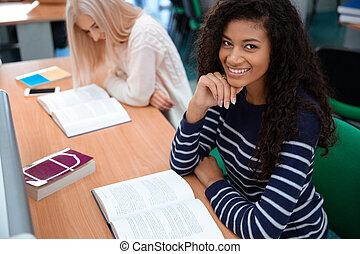 Female students reading books in university