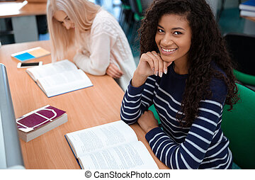 Female students reading books in university