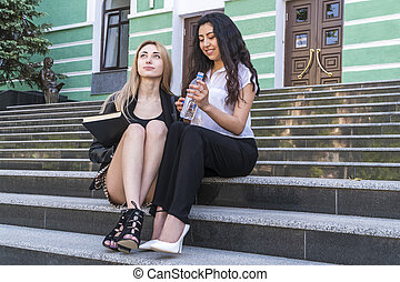 female students with book on the stairs