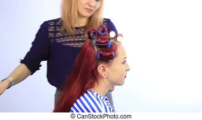 female stylist creating perfect hairstyle with large curls...