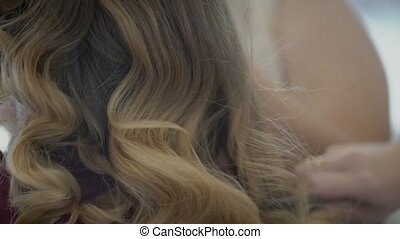 Female stylist is combing wavy hair of client sitting in...