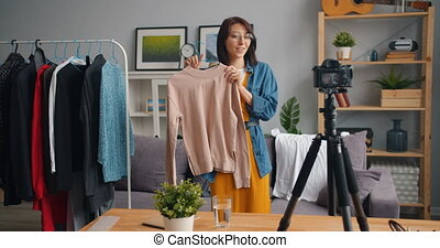 Female stylist recording video for online blog showing...