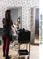 Female stylist standing and dyeing hair of young woman with paintbrush