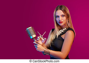 Female stylist standing with hairdresser's accessories -...