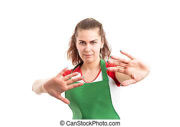 Female supermarket worker making defensive gesture