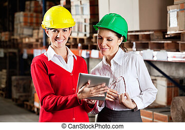 Female Supervisor With Colleague At Warehouse