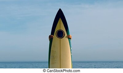 Female surfer peeking out from behind her board in slow...
