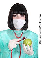 Female surgeon holding a green apple