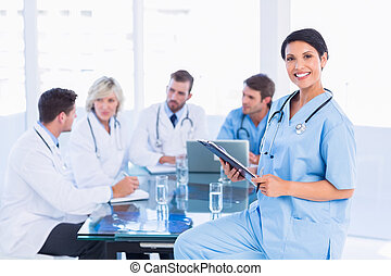 Female surgeon holding reports with colleagues in meeting