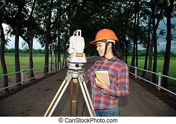 Female Surveyor or Engineer making measure on the field.