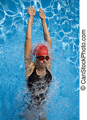 Athletic woman in swimming gear with blue swimming pool