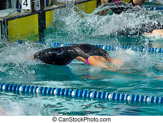 Female swimmer diving  into water at the start of a backstroke race
