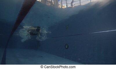 Female swimmer floating butterfly stroke in blue water pool...
