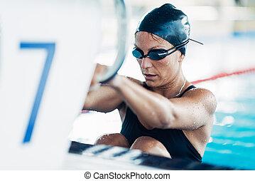 Female swimmer on starting block