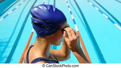 Female swimmer standing near pool side 4k