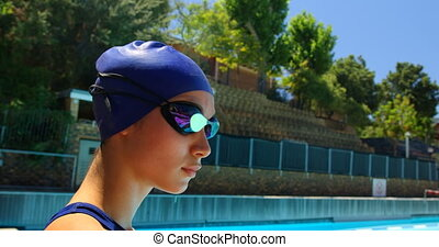 Female swimmer standing near poolside. Woman looking at camera 4k