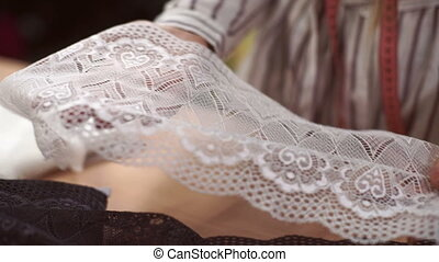 Female tailor demonstrates a broad band of white lace on his palms.