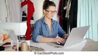 Female tailor using laptop at work - Young female in glasses...