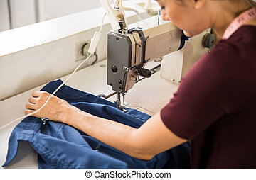 Female tailor using sewing machine