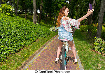 Female taking a selfie while sitting on her bike