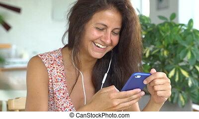 Female talking on phone smiling. Woman is speaking using white headphones.