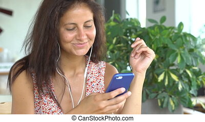 Female talking on phone with friend using white headphones